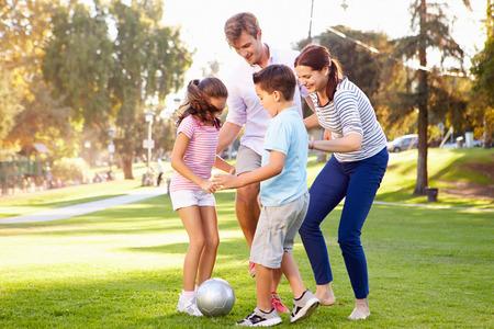 Familia que juega a fútbol en parque junto
