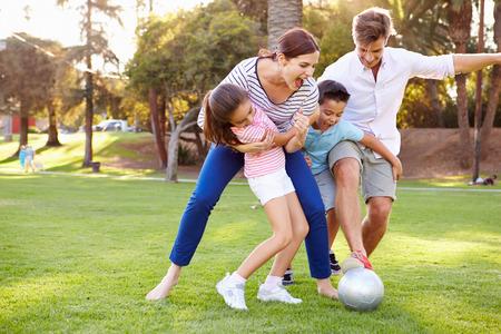 niños jugando en el parque: Familia que juega a fútbol en parque junto