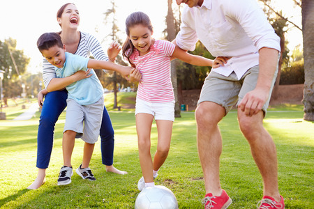 women playing soccer: Family Playing Soccer In Park Together Stock Photo