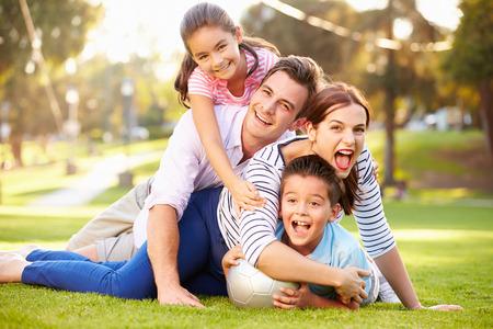 家庭: 家庭躺在草地上在公園一起
