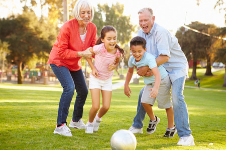 Grandparents Playing Soccer With Grandchildren In Park photo