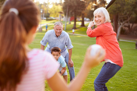 Grandparents Playing Baseball With Grandchildren In Park Stok Fotoğraf