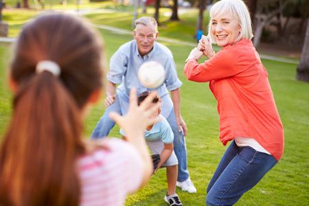 祖父母は孫と公園で野球 写真素材