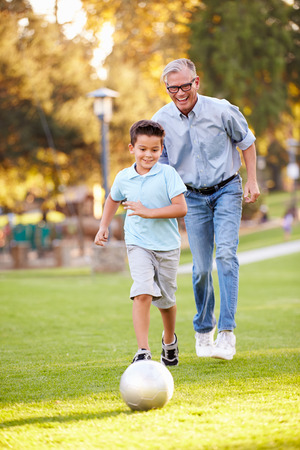 Grandfather Playing Football With Grandson In Park photo
