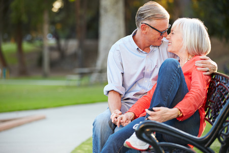Mature Romantic Couple Sitting On Park Bench Together photo