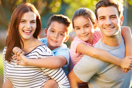 Outdoor Portrait Of Family Having Fun In Park Stock Photo
