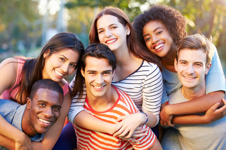 women hugging: Outdoor Portrait Of Young Friends Having Fun In Park Stock Photo