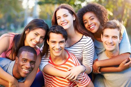 amigos abrazandose: Retrato al aire libre de jóvenes amigos que se divierten en el parque