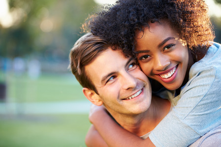 man carrying woman: Outdoor Portrait Of Romantic Young Couple In Park