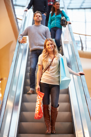 Female Shopper On Escalator In Shopping Mall photo