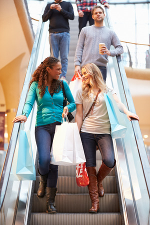 Two Female Friends On Escalator In Shopping Mall photo