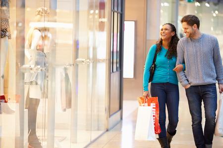 shopping: Pareja feliz llevando bolsas en centro comercial