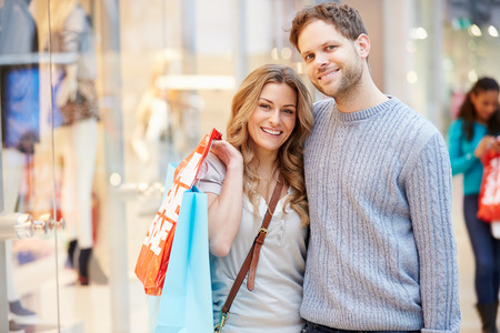 Portrait Of Couple Carrying Bags In Shopping Mall photo