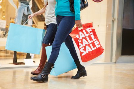 Close Up Of Shoppers Carrying Bags In Mall photo
