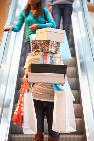 Woman Carrying Boxes And Bags In Shopping Mall photo