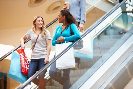 Twee vrouwelijke vrienden op roltrap in winkelcentrum Stockfoto