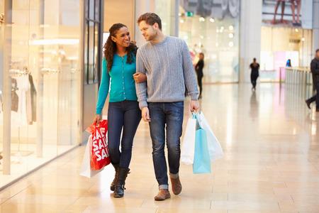 centro comercial: Pareja feliz llevando bolsas en centro comercial
