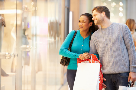 retail: Happy Couple Carrying Bags In Shopping Mall Stock Photo