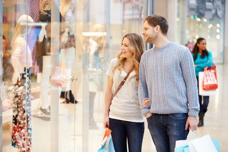 comprando: Pareja feliz llevando bolsas en centro comercial