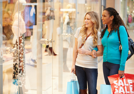 Two Female Friends Window Shopping With Bags photo