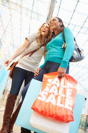 Two Female Friends With Bags In Shopping Mall photo
