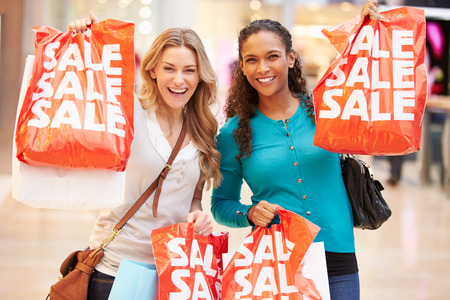 Two Excited Female Shoppers With Sale Bags In Mall Stock Photo