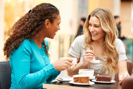 Two Female Friends Meeting In Cafe photo