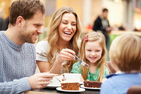 eating pastry: Family Enjoying Snack In Cafe Together Stock Photo