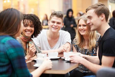 hombre tomando cafe: Grupo de amigos jovenes reuni�n en el caf�