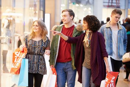 compras: Grupo de jóvenes amigos de compras en el centro comercial Juntos