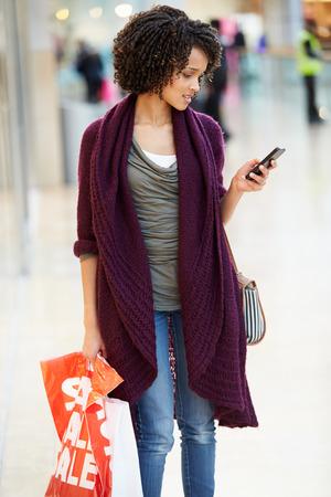 Vrouw in winkelcomplex met mobiele telefoon
