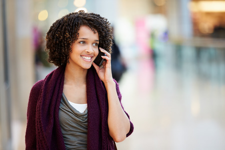 Frau im Einkaufszentrum unter Verwendung des Handys