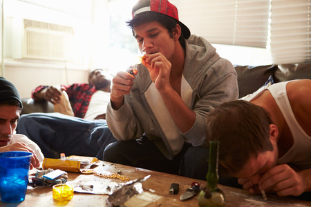 drug abuse: Gang Of Young Men Taking Drugs Indoors Stock Photo