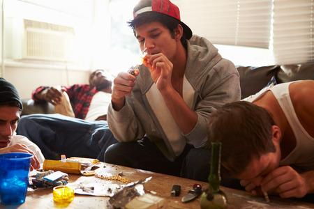 smoking pipe: Gang Of Young Men Taking Drugs Indoors Stock Photo