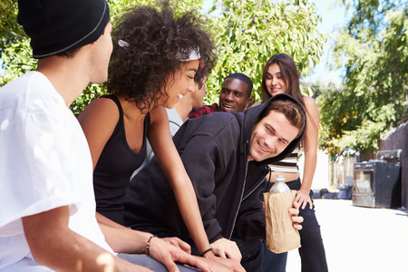 Gang Of Young People In Urban Setting Drinking Alcohol photo