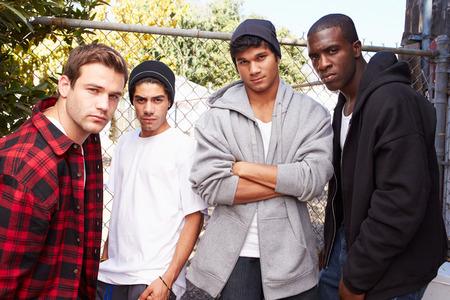 塀のそばに立って都市設定の若い男性のグループ