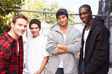 Group Of Young Men In Urban Setting Standing By Fence photo