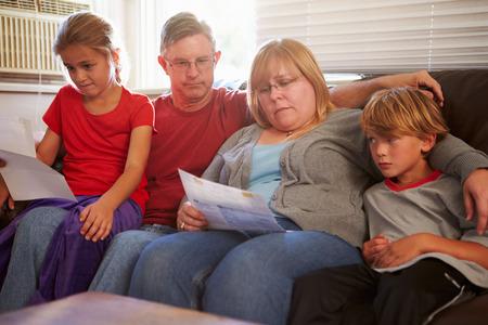 不幸な家族は手形を見てソファに座って 写真素材