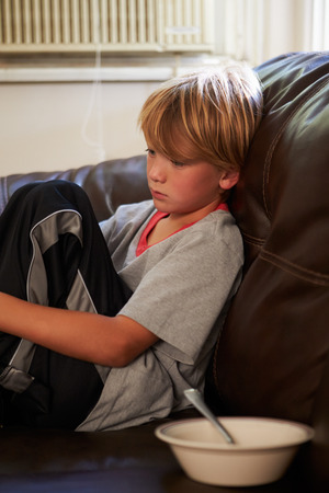Unhappy Boy Sitting On Sofa At Home photo