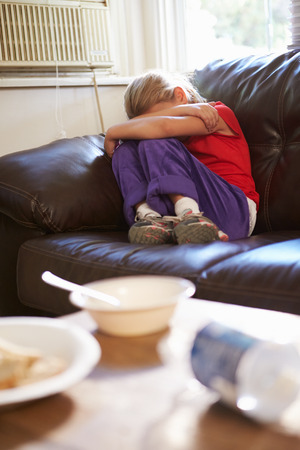 Unhappy Girl Sitting On Sofa At Home photo