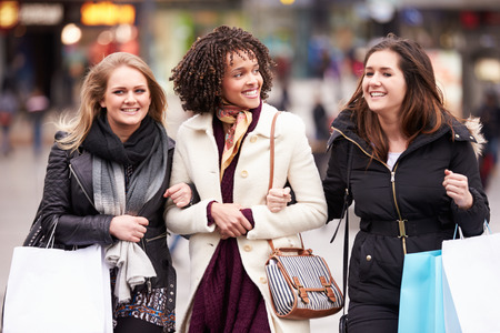 Three Female Friends Shopping Outdoors Together Imagens