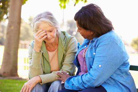 Woman Comforting Unhappy Senior Friend Outdoors