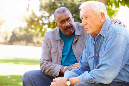 Man Comforting Unhappy Senior Friend Outdoors Stockfoto