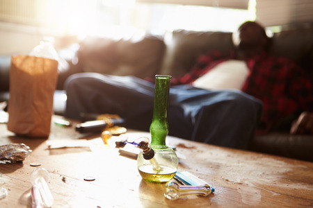 Man Slumped On Sofa With Drug Paraphernalia In Foreground Stock Photo