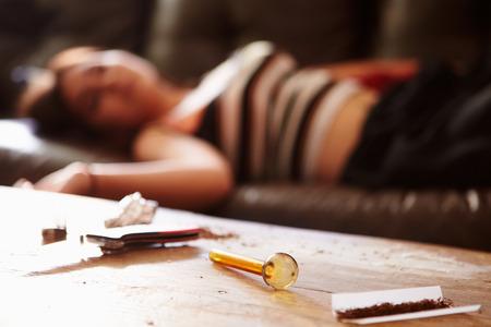 drogadiccion: Mujer tirado en el sofá con la parafernalia de drogas en primer plano