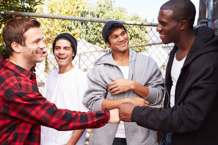 Group Of Young Men Greeting One Another In Urban Setting photo