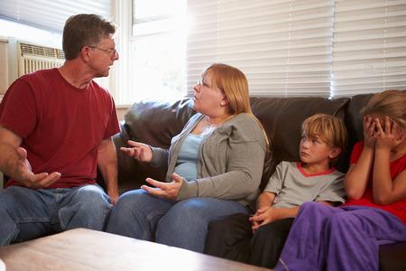 problemas familiares: Familia que se sienta en el sofá con los padres Argumentando