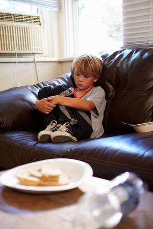 angry child: Unhappy Boy Sitting On Sofa At Home Stock Photo