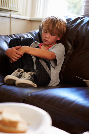 child poverty: Unhappy Boy Sitting On Sofa At Home Stock Photo