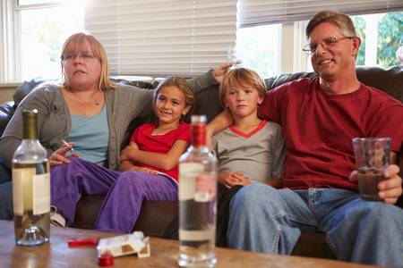 Parents Sit On Sofa With Children Smoking And Drinking